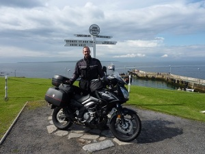 Adrian with motorbike in front of street sign in Scotland