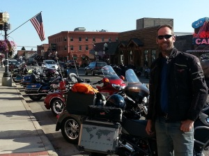 Adrian and his GSA r1200 next to a row of Harley Davidson motorbikes