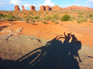 Loz and Adie's shadow with Arches National Park in the background