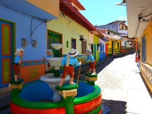 A brightly coloured fountain in front of brightly painted buildings in Guatape