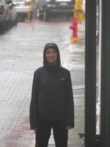 Lauren standing in the rain wearing a waterproof jacket
