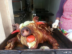A roast pig on a spit with chillis in its ears