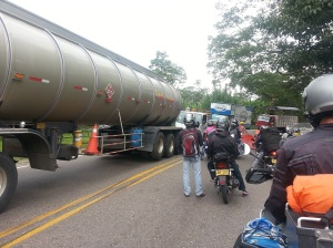 A group of motorbikers waiting as trucks go past