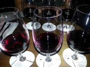 Glasses of red wine lined up on a table